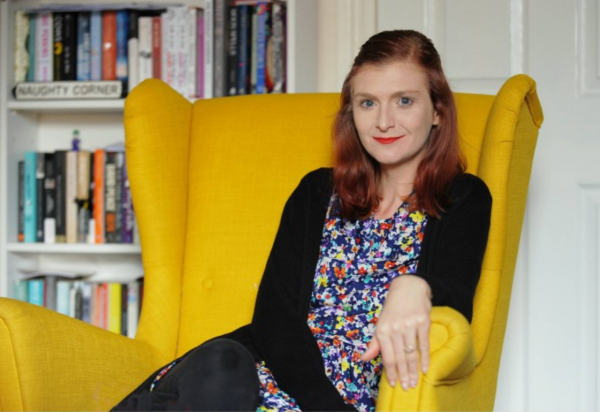 portrait of Rachel Charlton-Dailey sat in an armchair in front of a bookcase