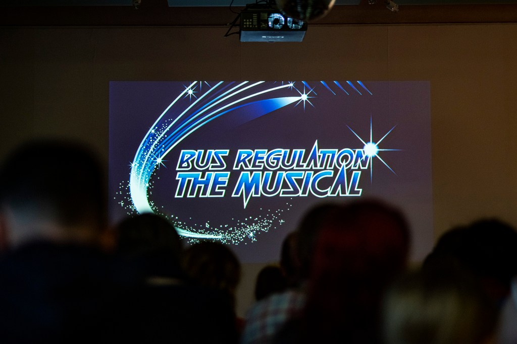 A projected logo that states 'Bus Regulation: the Musical' in front of a seated audience
