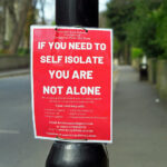A red poster fastened to a lamppost that reads 'IF YOU NEED TO SELF ISOLATE YOU ARE NOT ALONE' followed by contact details for the local mutual aid group