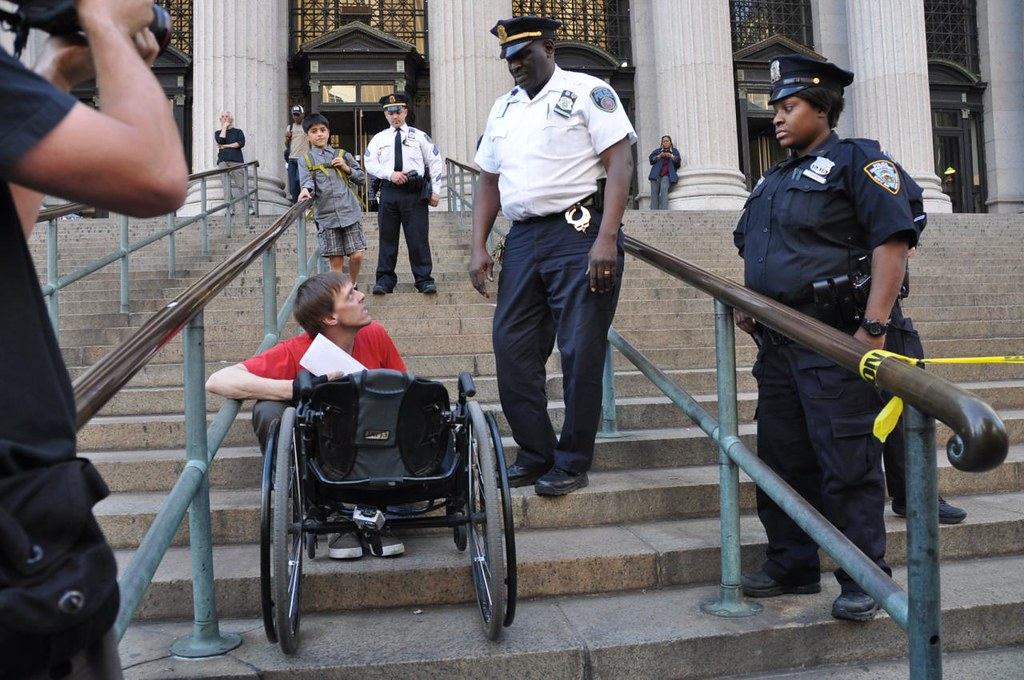 A man is sat on the stairs of a US Government building, holding onto his wheelchair. He is in conversation with a police officer who is standing above him, whilst two other police officers and several civilians stand and watch.