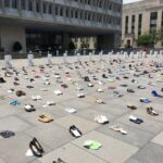 Pairs of shoes are laid out in front of a local government protest as part of a 'Millions Missing' protest.
