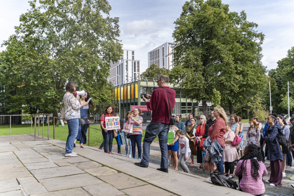 A speaker stands on the stop of some steps, addressing the crowd via megaphone, in Coventry city centre. One person in the crowd holds a sign reading 'CREATIVE KINDNESS - TACKLING ISOLATION'