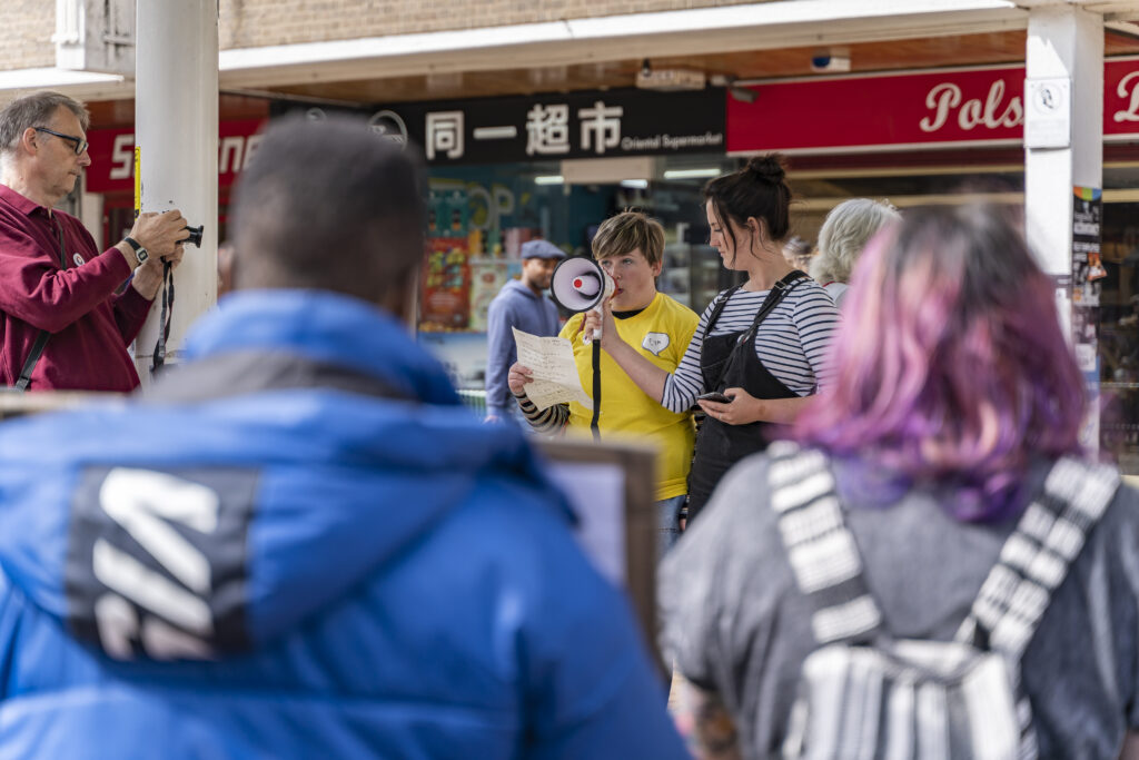 A member of Coventry Youth Activists speaks through a megaphone held by another person to a crowd in the middle of the city centre.