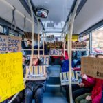 A group of passengers sat on a bus holding up placards stating 'We need public control of our buses', 'bus companies are taking us for a ride', 'better buses for Greater Manchester', 'EASY', 'Acessible', 'AFFORDABLE