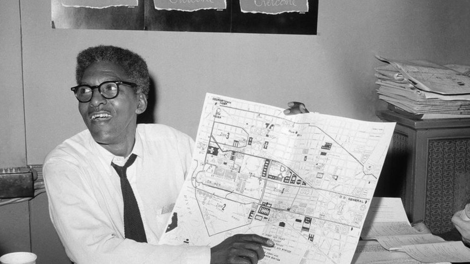Bayard Rustin holding a map and smiling. He knows some fudging magic is going to happen.
