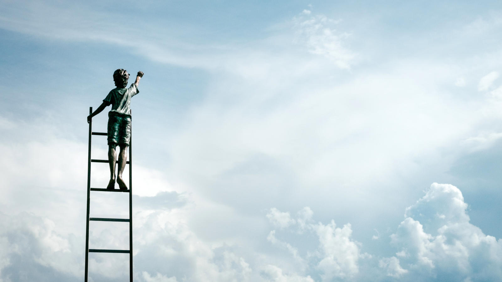 Boy on a ladder in the clouds