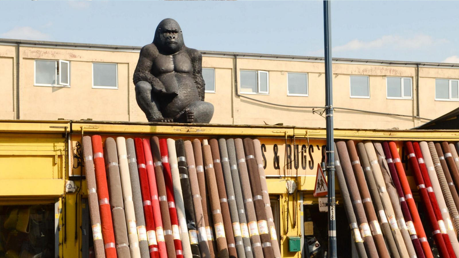 A big gorilla on top of a carpet shop