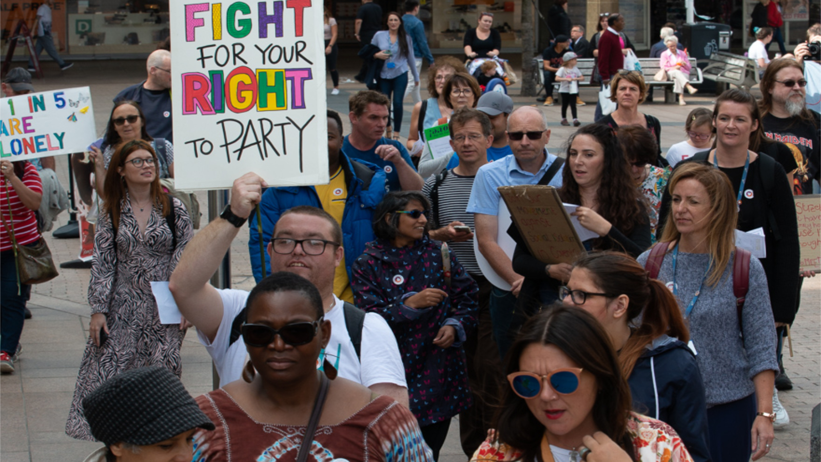 Walk and Talk 2019: Sign in the air saying fight for our right to party. Lots of people walking
