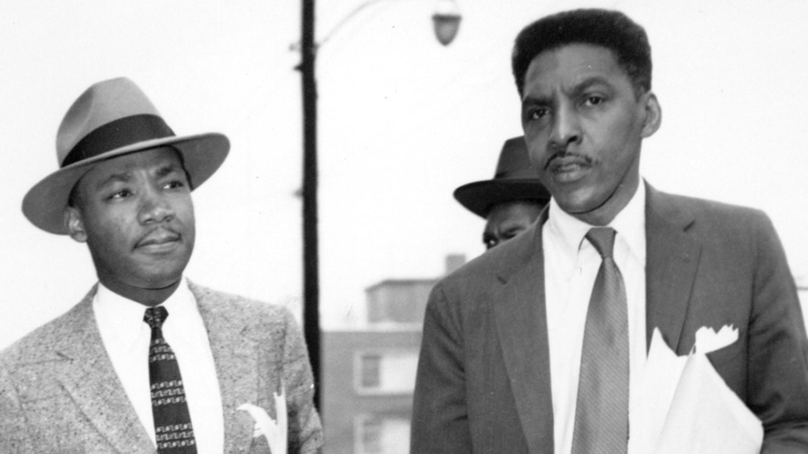 Bayard Rustin with Martin Luther King by a staircase.
