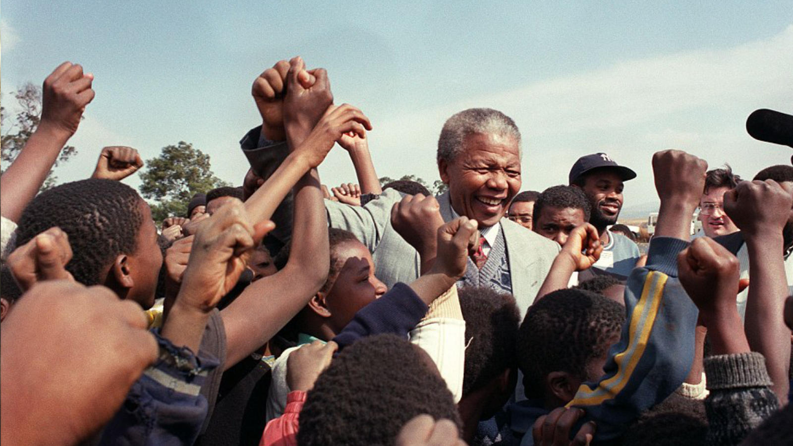 Nelson Mandela with young people in a crowd. Sun is shining.