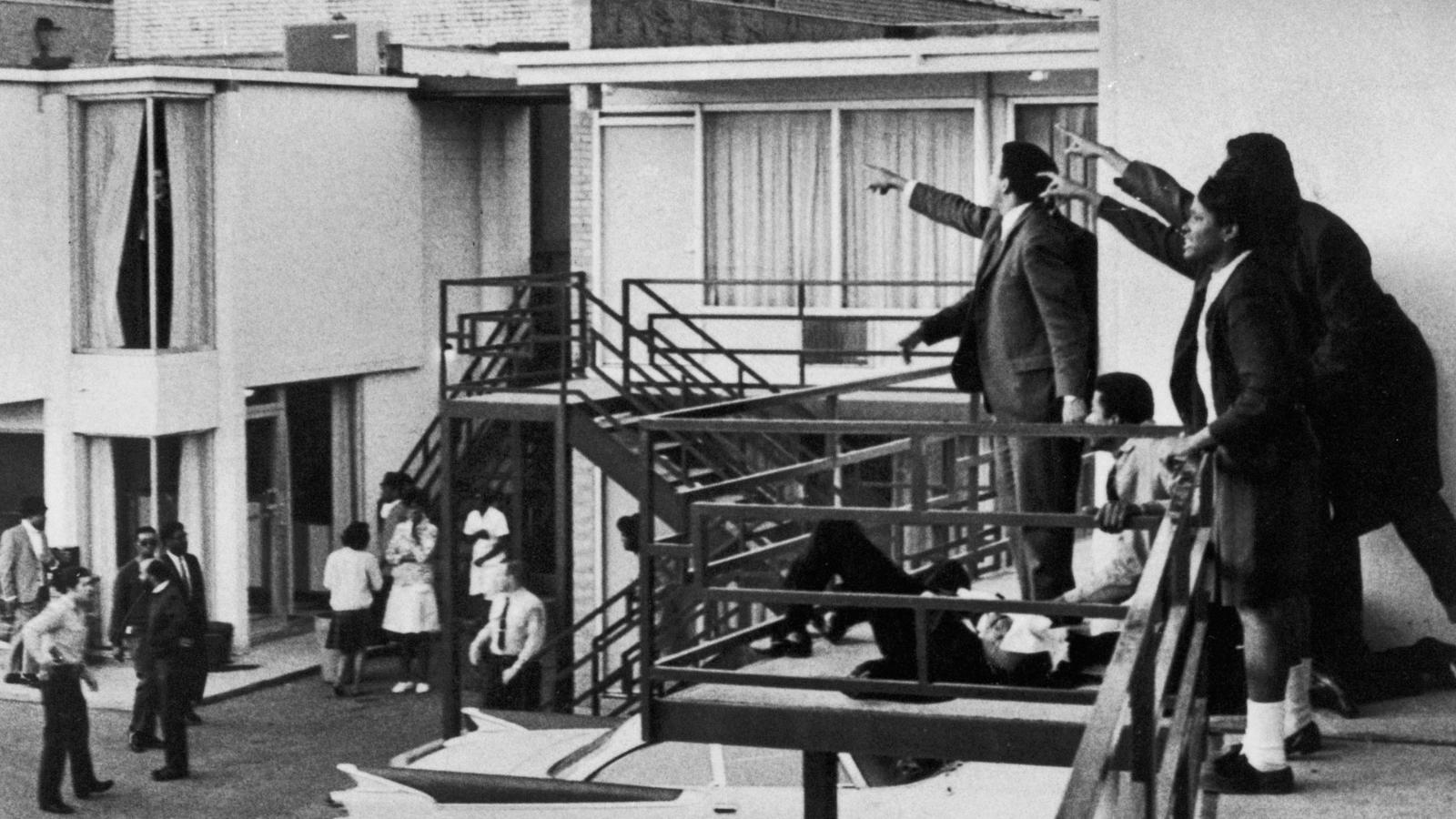 Image of Martin Luther King on the floor with people around him on a balcony - pointing to where the gunman shot him.