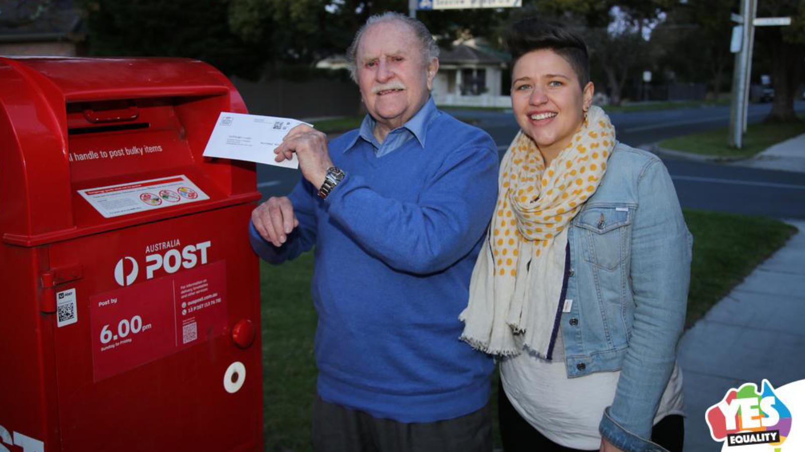 Man and woman posting into a red letter box. Image, Craig Dwyer