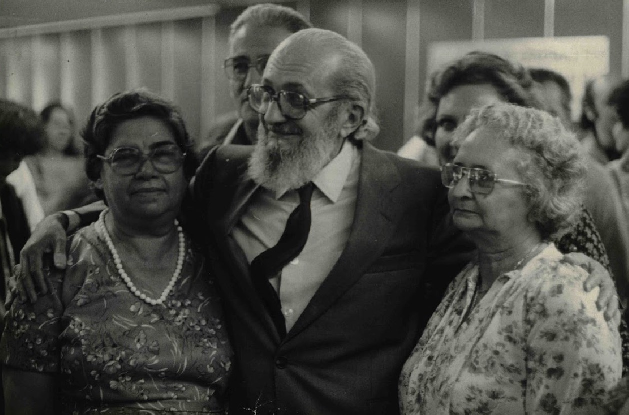 Paulo Freire arms around two elderly ladies, smiling.